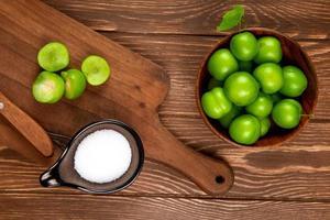 Vista superior de ciruelas verdes ácidas en un recipiente de madera con una tabla de cortar y sal foto