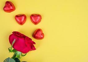 Chocolates en forma de corazón y una rosa sobre un fondo amarillo