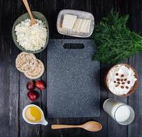 Top view of a cutting board surrounded with cheese and other foods photo