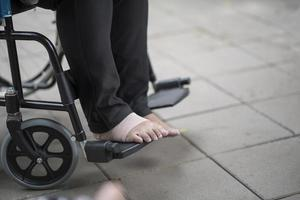 Close-up of an elderly person in a wheelchair with painful foot