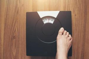 Woman's feet standing on weight scale photo