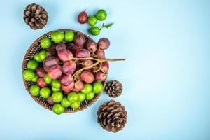 Vista superior de uvas frescas con ciruelas ácidas en una canasta de mimbre