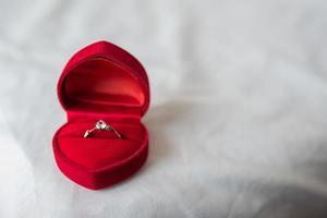 anillo de bodas en una caja en la cama foto