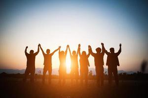 Silhouette of happy team joining hands in the air photo