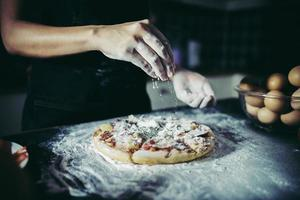 Manos del chef vertiendo harina sobre masa cruda