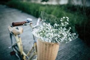 Bicicleta vintage con una canasta llena de flores silvestres
