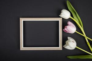 Top view of an empty picture frame and tulips