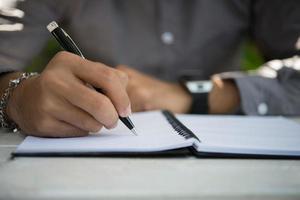Hombre escribiendo en el bloc de notas mientras está sentado relajándose en el jardín de su casa