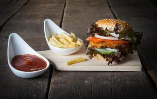 Rustic homemade hamburger and french fries with tomato sauce