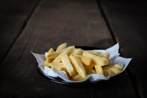 Tasty french fries on wooden table background