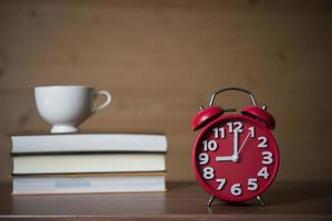 Alarm clock at 9am and a stack of books with coffee
