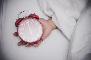 Hand setting the alarm clock at 6 o'clock