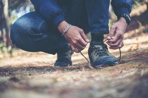 Hombre joven excursionista ata los cordones de sus zapatos mientras viaja con mochila en el bosque