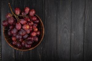 Vista superior de las uvas rojas en una canasta de mimbre sobre fondo de madera oscura.