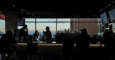 Silhouette of people inside a bar
