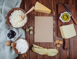 Vista superior de papel marrón con queso y otros aperitivos.