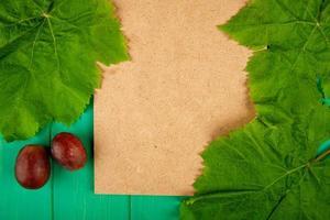 Vista superior de papel marrón con uvas y hojas verdes.
