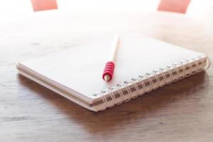 Notebook and a red pencil in sunlight