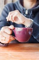 persona sosteniendo una taza de café morada
