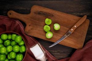 Top view of a wooden cutting board with a knife and sour plums