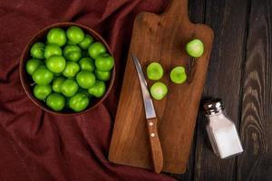 Vista superior de ciruelas verdes ácidas en un recipiente y sobre una tabla para cortar