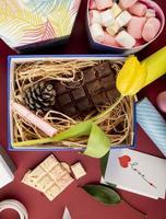 Vista superior de una caja con flores, chocolate y dulces.