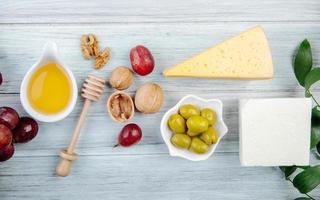 Vista superior de queso con miel, uvas, nueces y aceitunas.