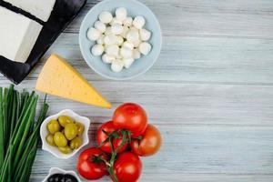 Vista superior de queso con tomates frescos y aceitunas en escabeche
