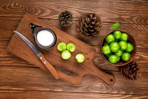 Top view of a cutting board with sour plums and pinecones
