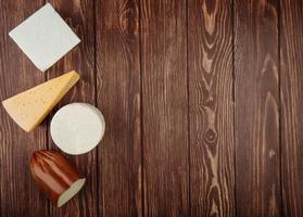 Vista superior de queso sobre un fondo de madera rústica con espacio de copia
