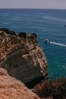 Boat cruising near a cliff photo