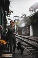 Man standing on train rail during daytime