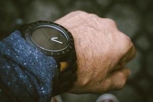 Black analog watch in left human wrist