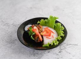 Spicy sardine dish in black ceramic bowl