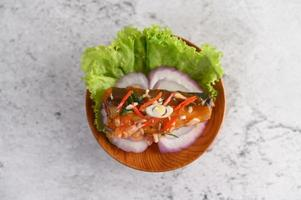 Spicy sardine salad in a wooden bowl