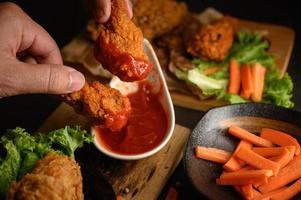 Sumergir a mano pollo frito crujiente en salsa foto