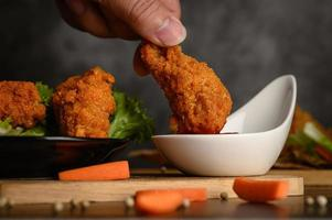 Hand dipping crispy fried chicken into sauce