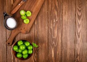 Top view of sliced green plums with salt and kitchen knife on a wooden surface