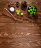 Top view of sliced green plums with salt and kitchen knife on a wooden table