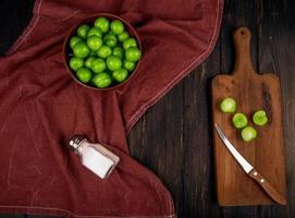 Vista superior de ciruelas verdes ácidas en un recipiente y ciruelas en rodajas sobre una tabla de cortar de madera