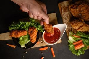 Hand dipping crispy fried chicken into sauce photo