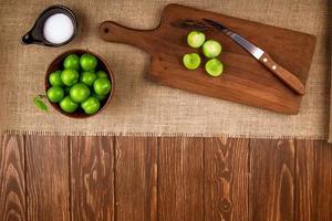 Vista superior de ciruelas verdes ácidas en un recipiente y sobre una tabla de cortar de madera
