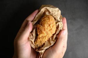 persona sosteniendo un muslo de pollo frito