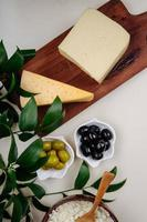 Vista superior de queso y aceitunas sobre un fondo blanco.