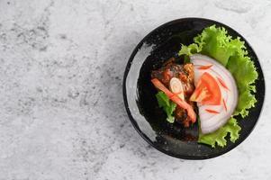 Plato de sardina picante en cuenco de cerámica negra foto