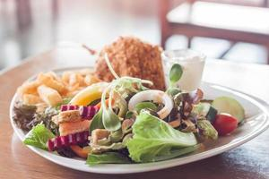 Plate of salad with fried fish and french fries