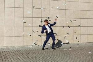 Man in a suit dancing in money photo