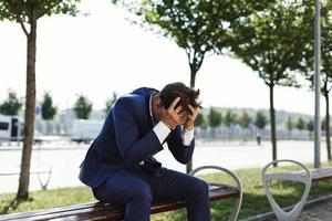 hombre de negocios triste se sienta afuera