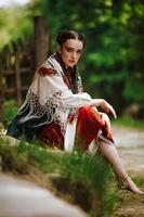 Hermosa joven sentada en un parque con un colorido vestido ucraniano
