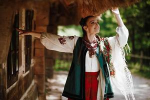 Young girl in a colorful Ukrainian dress dances and smiles photo